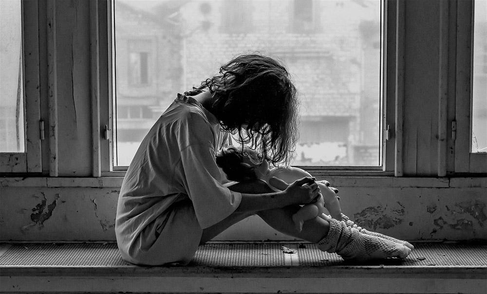 Emotionale Gewalt: Verzweifelte Frau sitzt auf einer Fensterbank