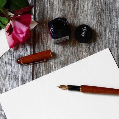 Blog: Schreibtisch mit Briefpapier, einem Füller, einem Tintenfass und einer Rose