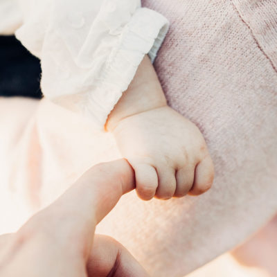 Slider Babyhand greift Zeigefinger der Mama